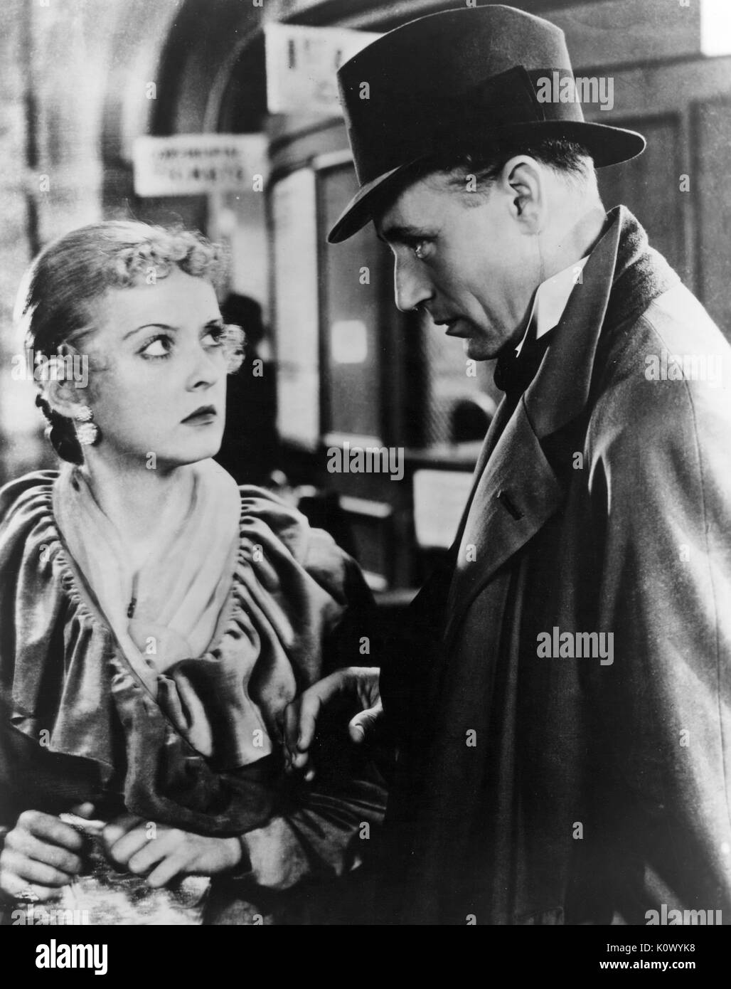 Bette Davis and an unidentified man in a movie still, the man wearing a hat and appearing threatening, Bette Davis with a concerned, defiant expression, 1949. Photo credit Smith Collection/Gado/Getty Images. - Stock Image