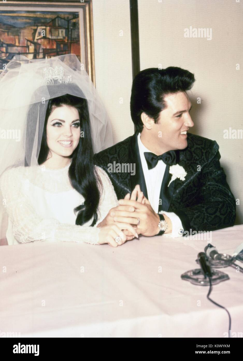 Elvis Presley and Priscilla Presley wedding photo, wearing tuxedo and wedding dress, smiling and holding hands, during a press conference following their marriage, May, 1967. Photo credit Smith Collection/Gado/Getty Images. - Stock Image