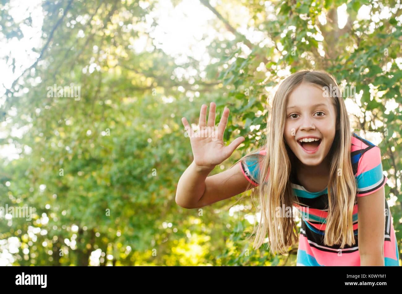 Girl waving hello - Stock Image
