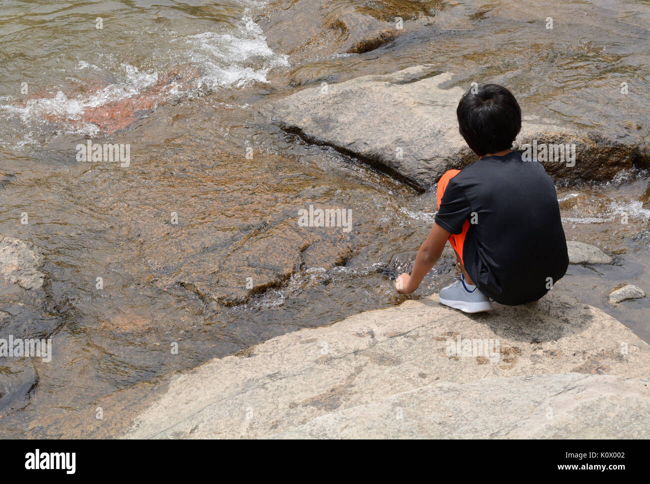 Young boy watching current of river flow down stream over rocks - Stock Image