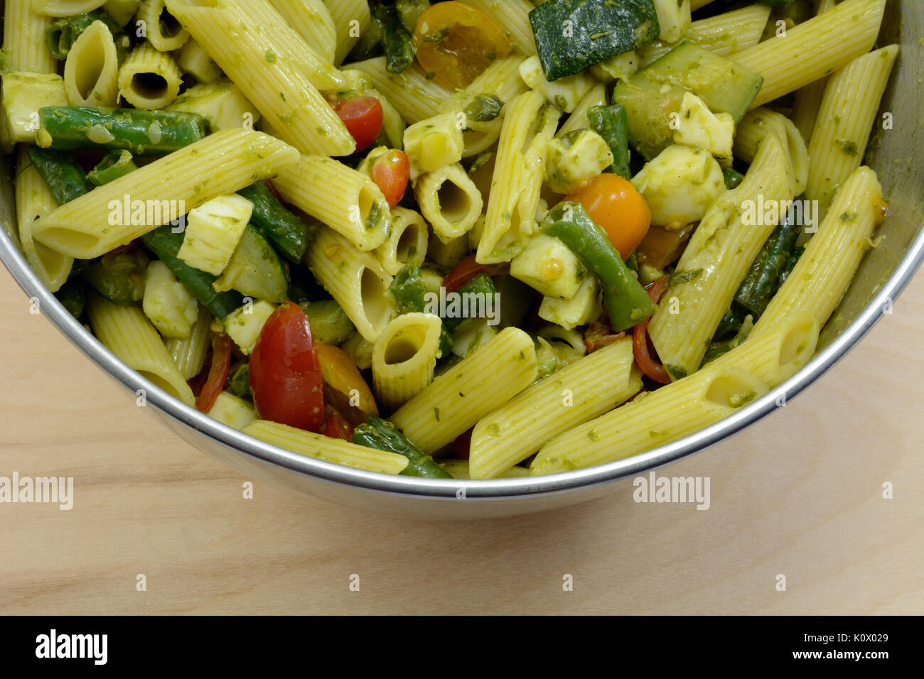 Close up of pesto penne pasta salad with zucchini, tomatoes, green beans and mozzarella cheese in mixing bowl Stock Photo