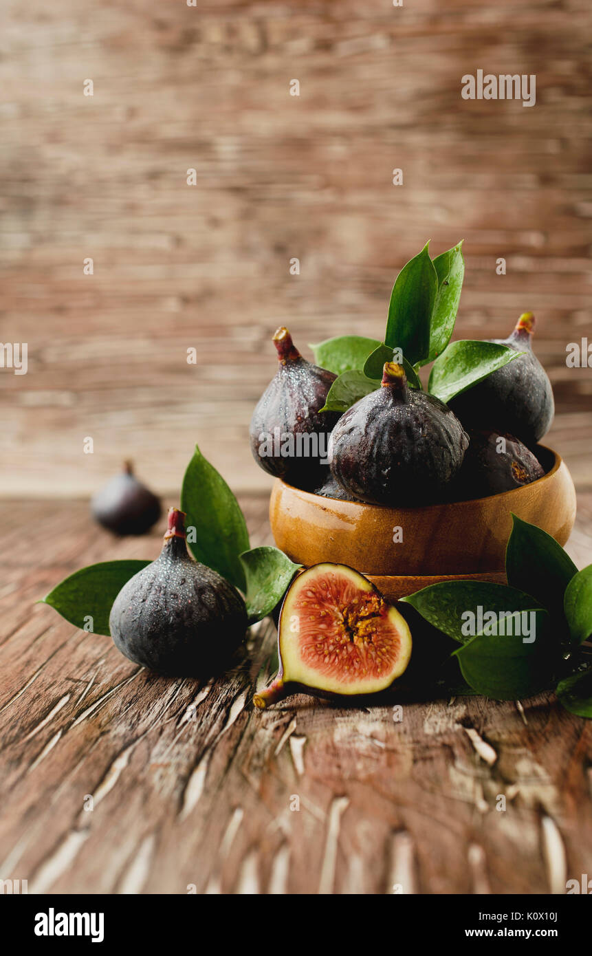 raw figs in wooden bowl on the table, selective focus - Stock Image