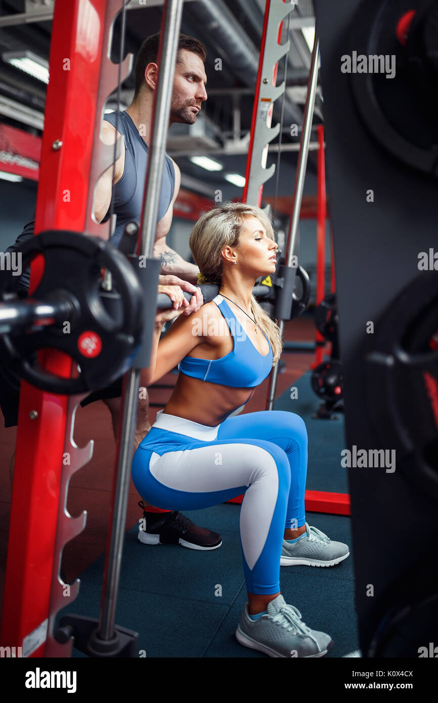 Sporty girl doing squat exercises with assistance of her personal trainer at gym. - Stock Image