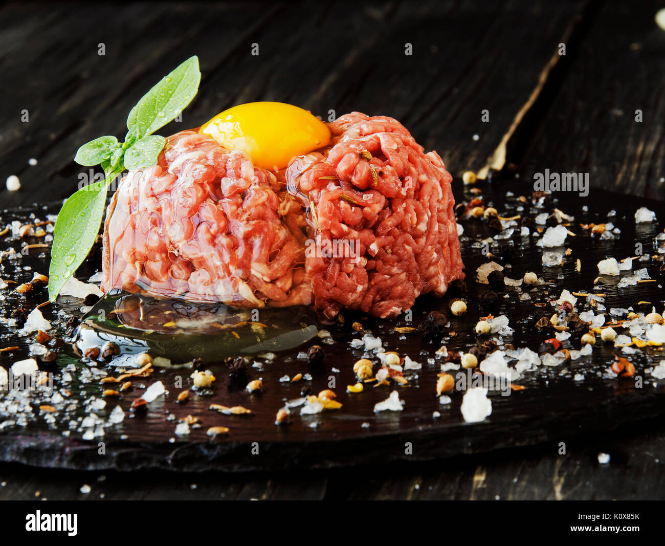 raw minced meat, vegetables with salt and spices, on a black background, selective focus, space for text - Stock Image