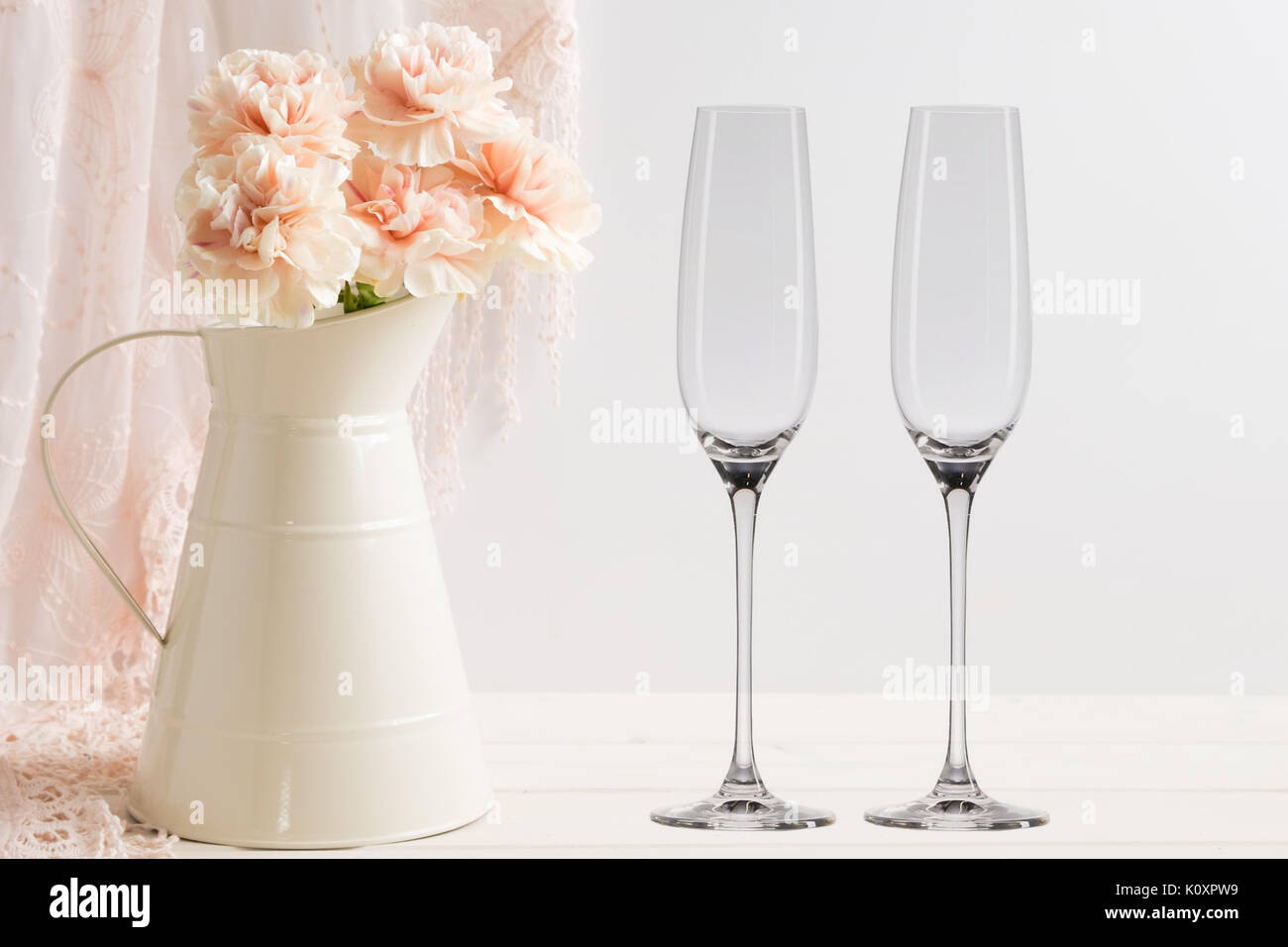 Floral mock-up of 2 champagne glasses next to a vase of flowers, perfect for businesses who sell decals, vinyl stickers, just overlay your design - Stock Image
