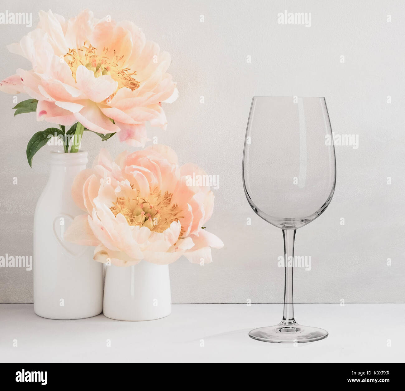 Floral mock-up of 1 wine glass next to a vase of flowers, perfect for businesses who sell decals, vinyl stickers, just overlay your design - Stock Image
