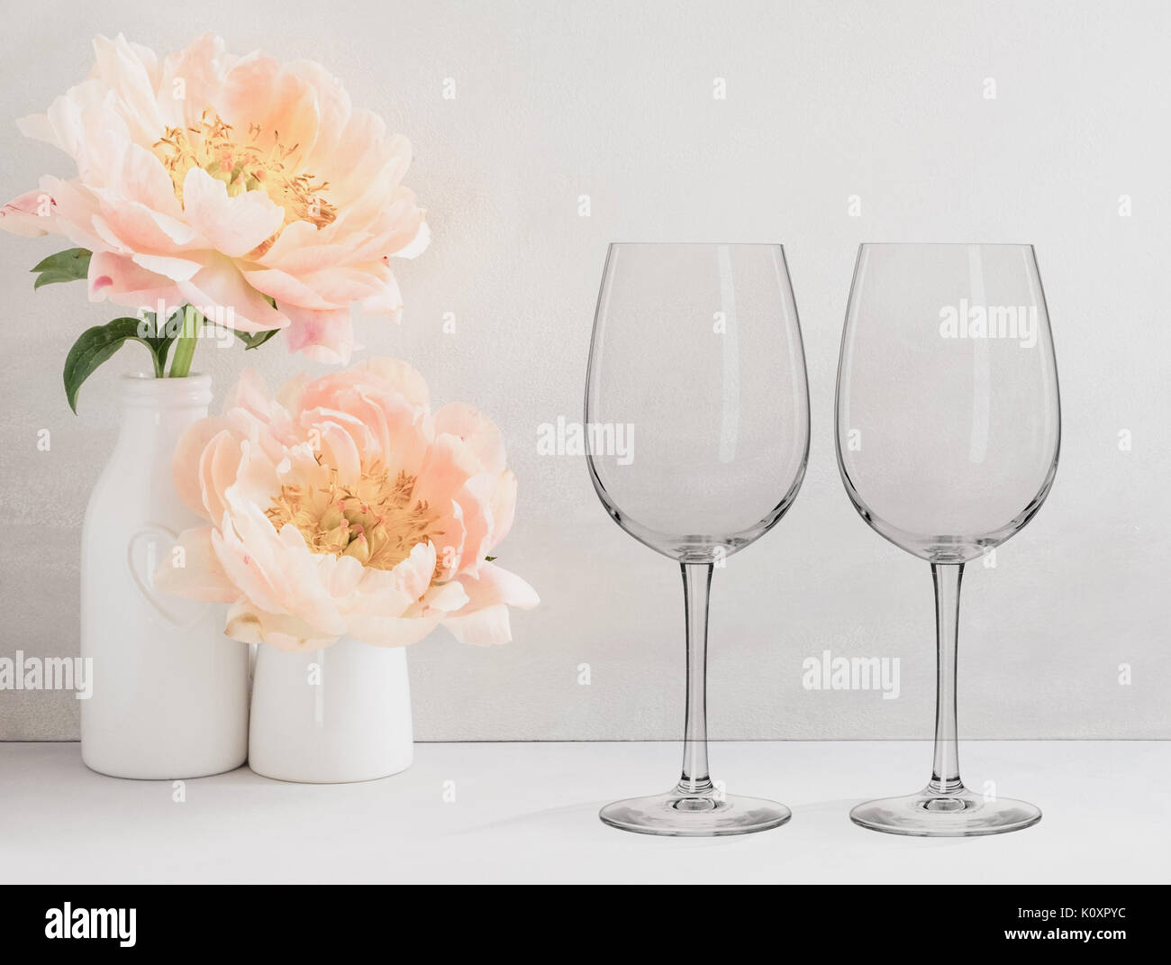 Floral mock-up of 2 wine glasses next to a vase of flowers, perfect for businesses who sell decals, vinyl stickers, just overlay your design - Stock Image