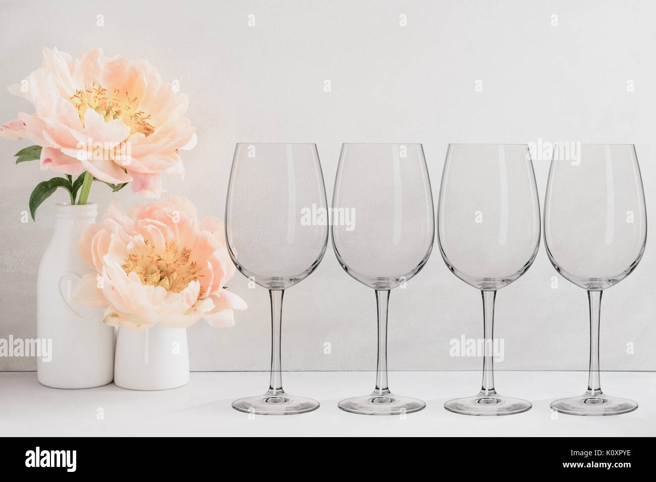 Floral mock-up of 4 wine glasses next to a vase of flowers, perfect for businesses who sell decals, vinyl stickers, just overlay your design - Stock Image