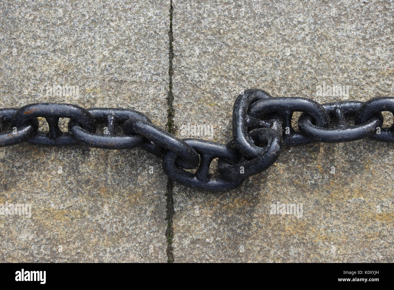 A black metal chain with large links lies on concrete slabs on the ground. - Stock Image