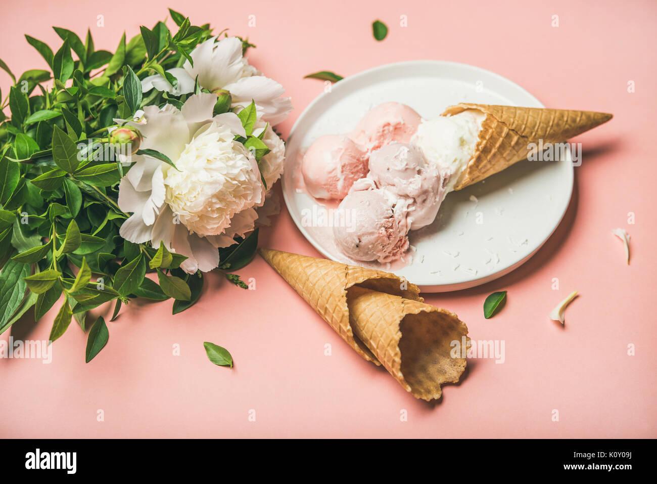 Strawberry and coconut ice cream, cones, white peony flowers Stock Photo