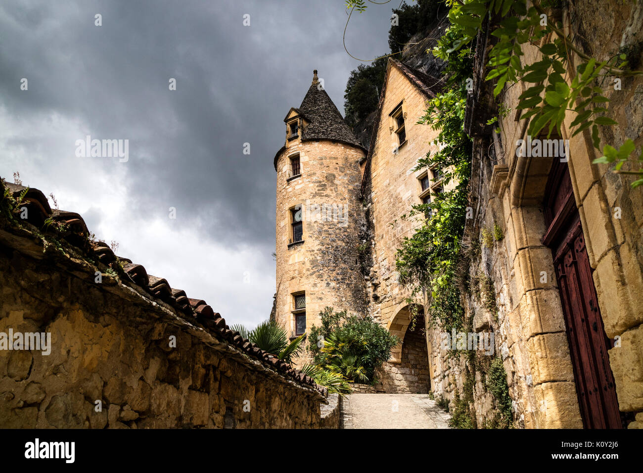 The 15th Century Renaissance Style Manoir de Tarde in the Village of La Roque-Gageac, Set Against a Dramatic Stormy Sky, Dordogne, France, Europe - Stock Image