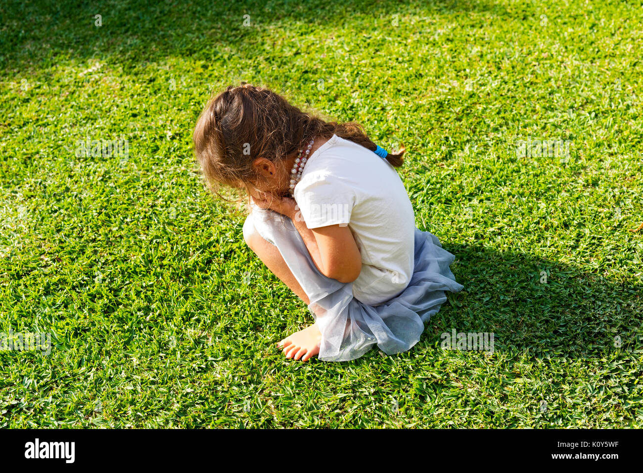 A young girl having a tantrum and crying on the lawn Stock Photo