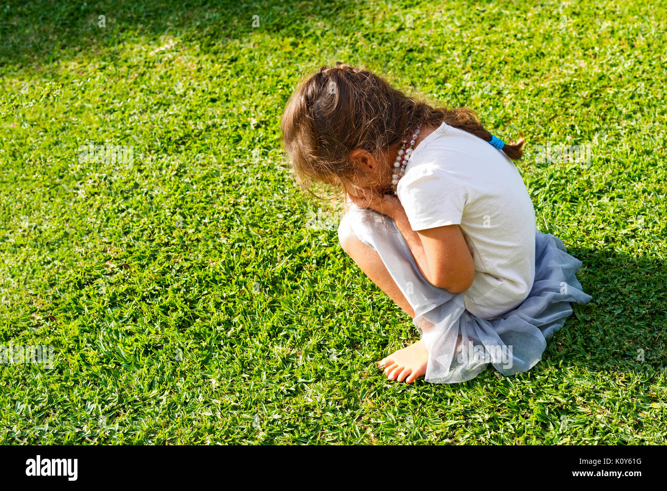 A young girl having a tantrum and crying on the lawn - Stock Image