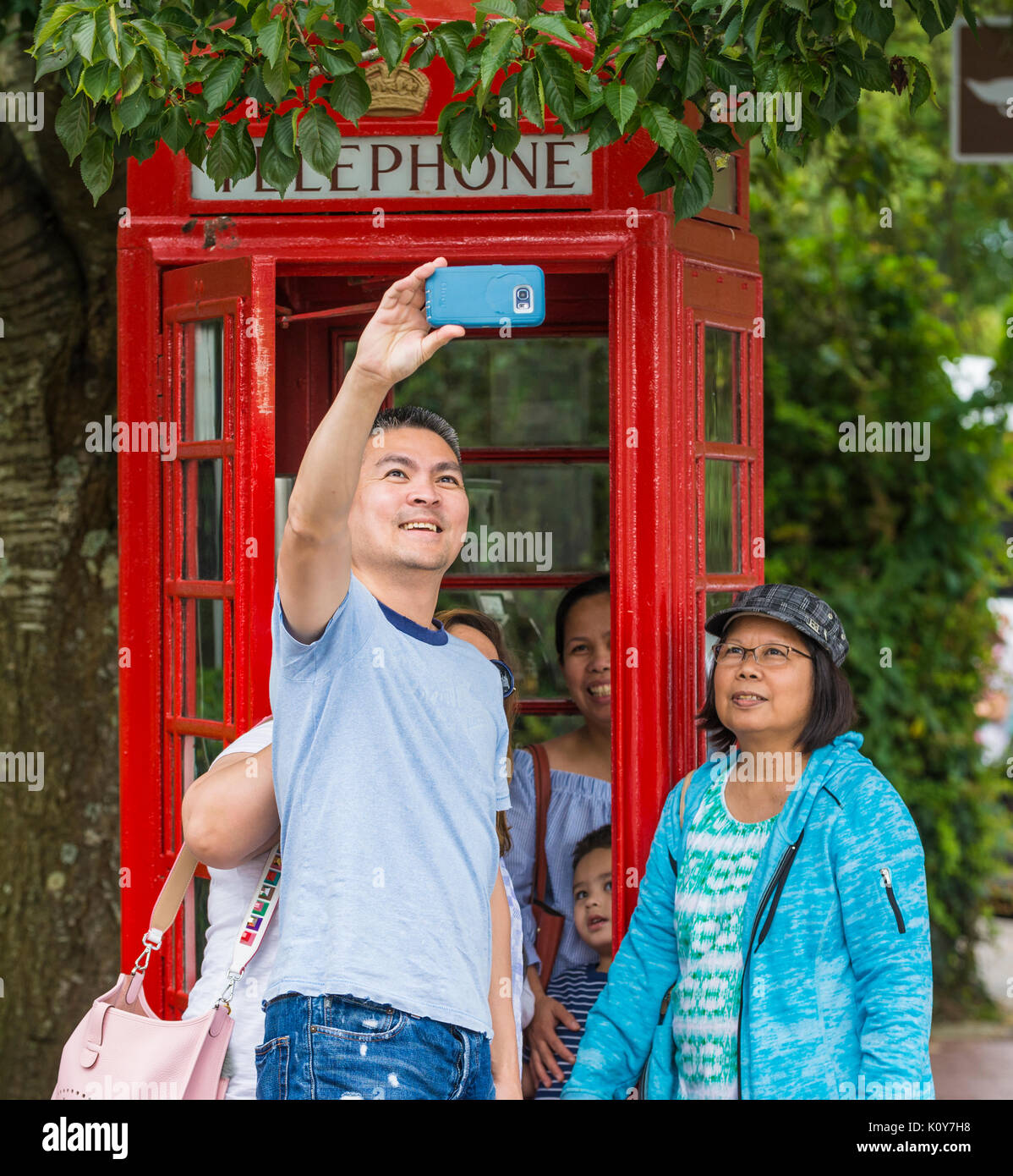 Asian family of tourists taking a selfie outside a red telephone box in Arundel, West Sussex, England, UK. - Stock Image