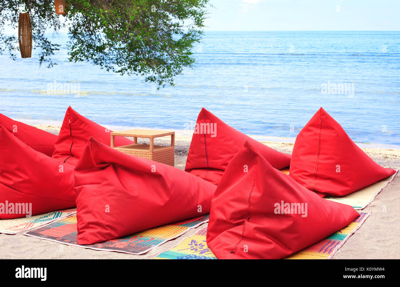 A lot of red Bean bags and table set on the ocean beach - Stock Image