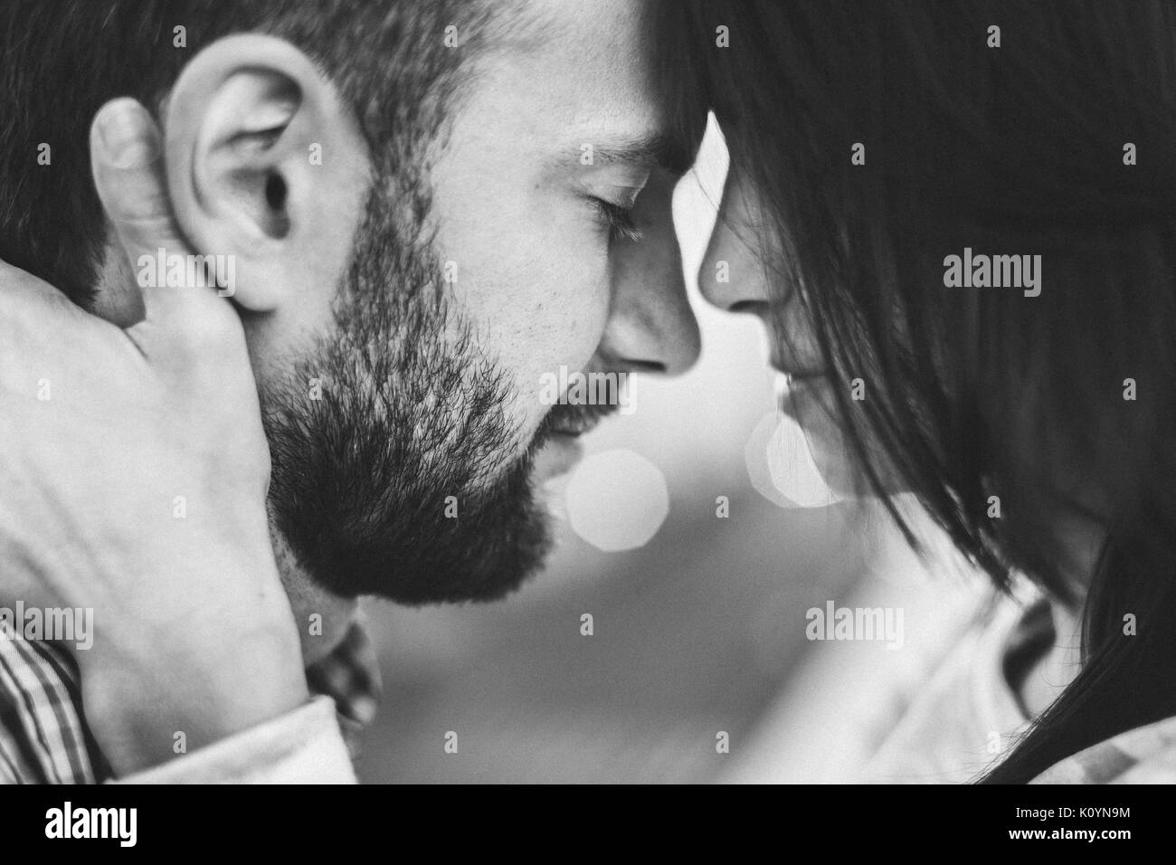 Gentle close-up portrait of man and woman together, happy, looking at each other. Black and white toning - Stock Image