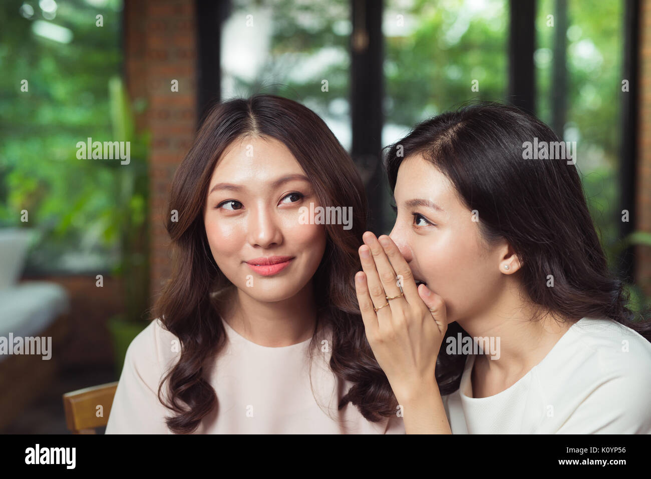 Portrait of a girl telling secrets to her amazed friend in the living room at home - Stock Image