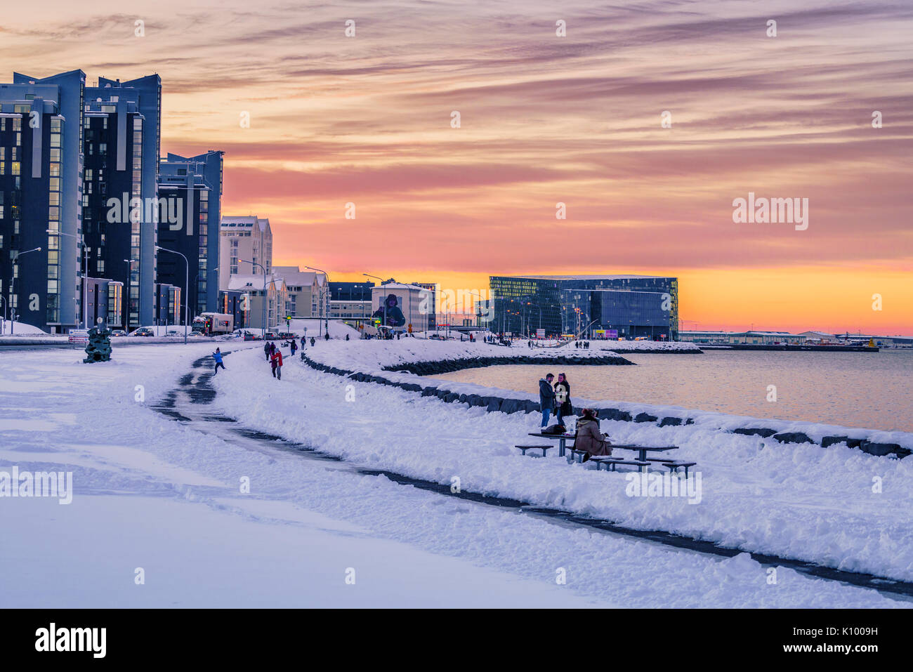 Walking path along the sea in the wintertime, Harpa in the backgrounsd Reykjavik, Iceland - Stock Image