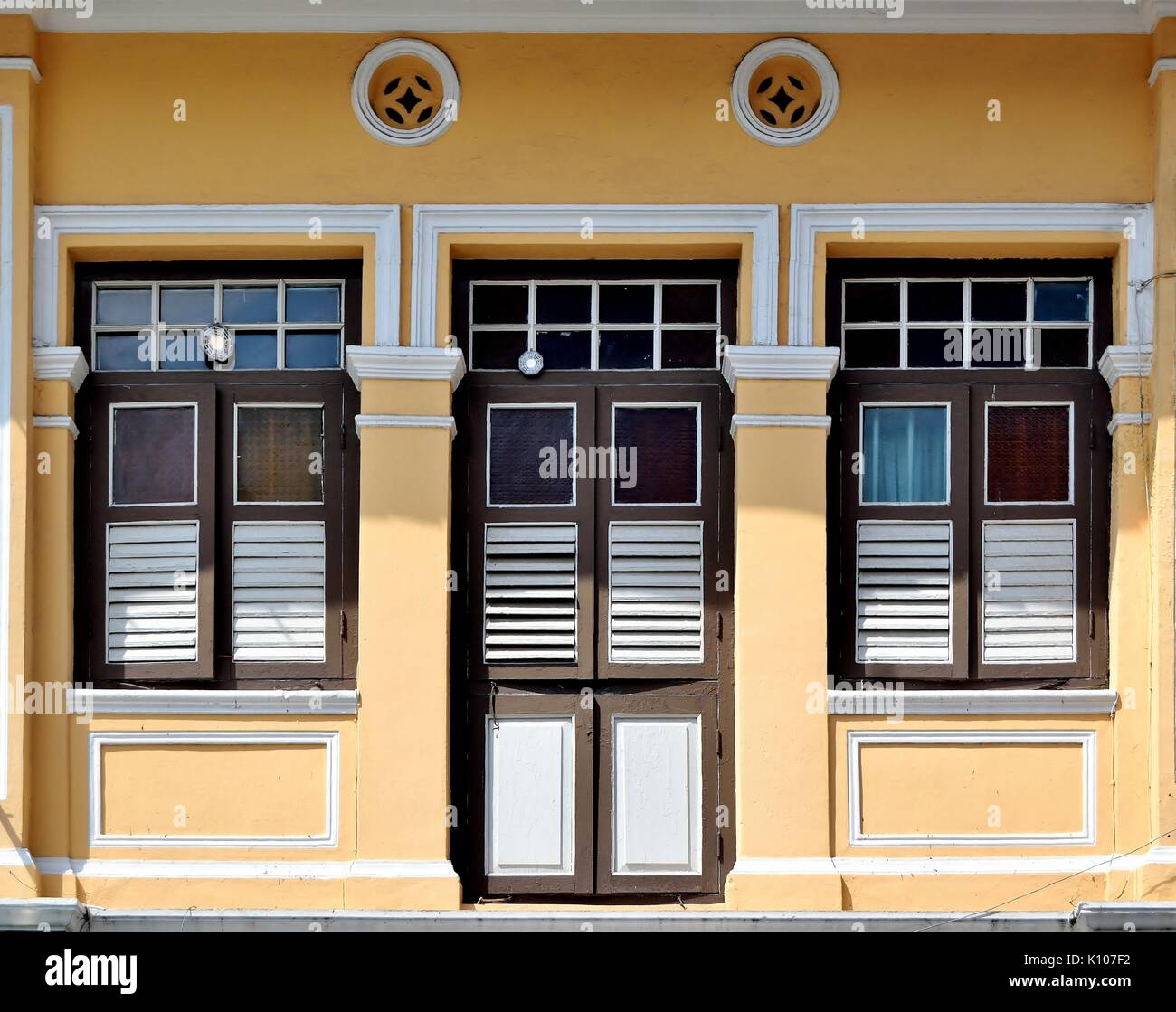 Traditional shop house exterior with brown wooden louvered shutters ...