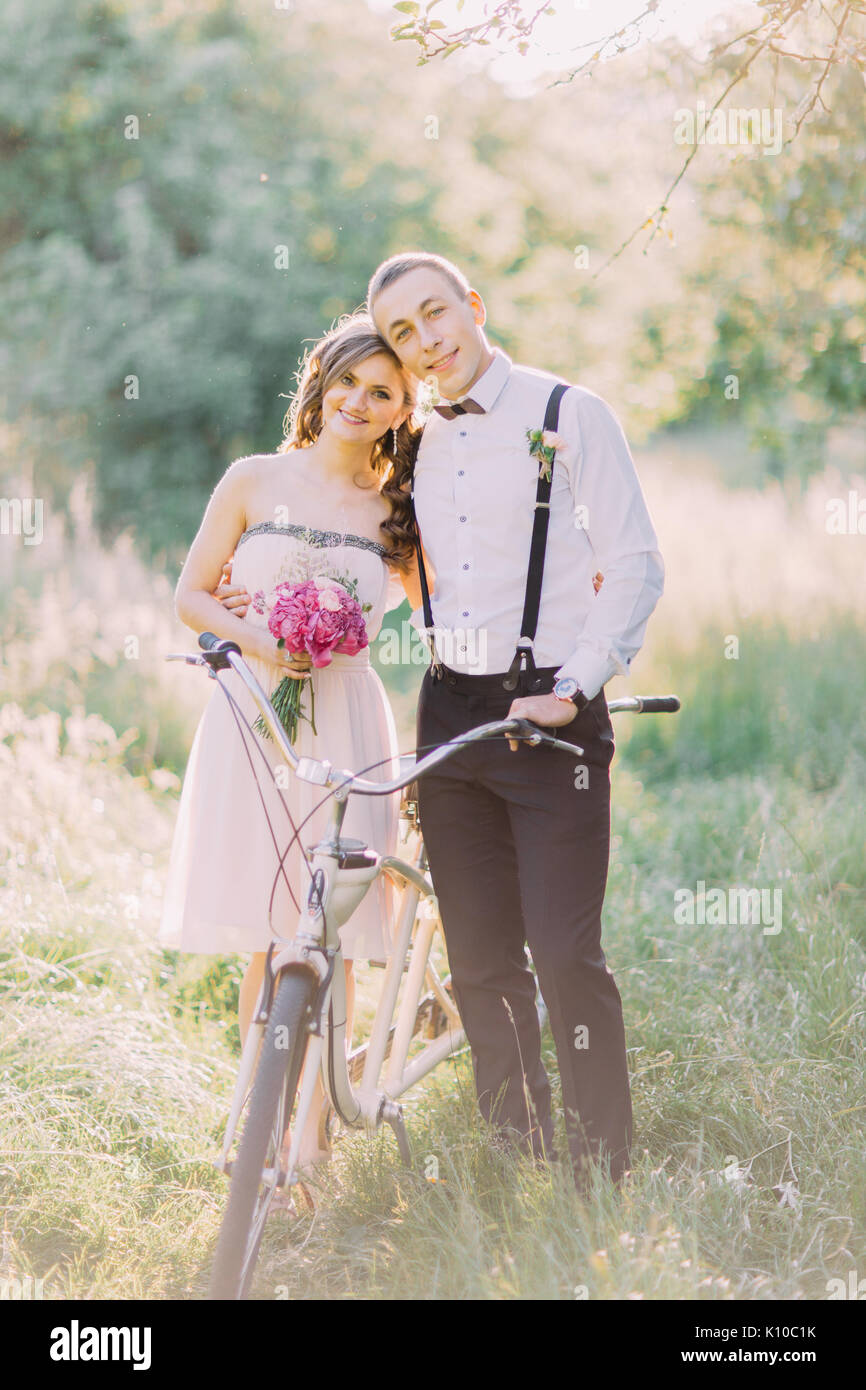 The vertical photo of the bridesmais and the best man hugging, holding the pink bouquet and the bicycle in the spring Stock Photo