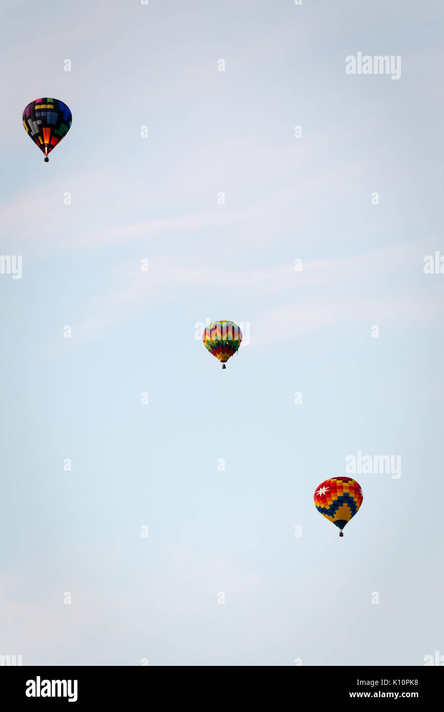 Three colorful hot air balloons float in  a row away into the sky Stock Photo