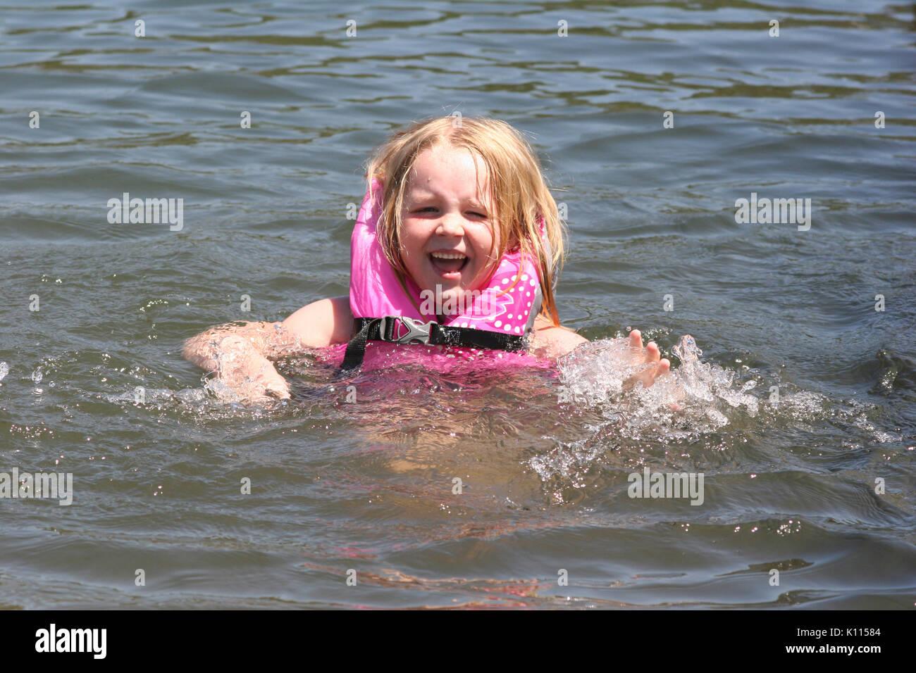 GIRL (6) WEARING LIFE JACKET AND SWIMMING IN LAKE SACRAMENTO COUNTY, CALIFORNIA - Stock Image