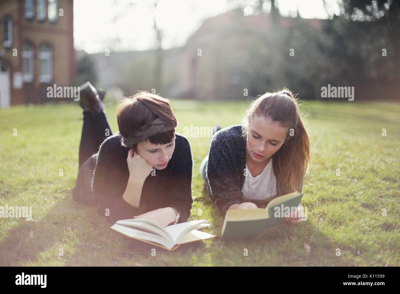 Two young women reading in a park - Stock Image