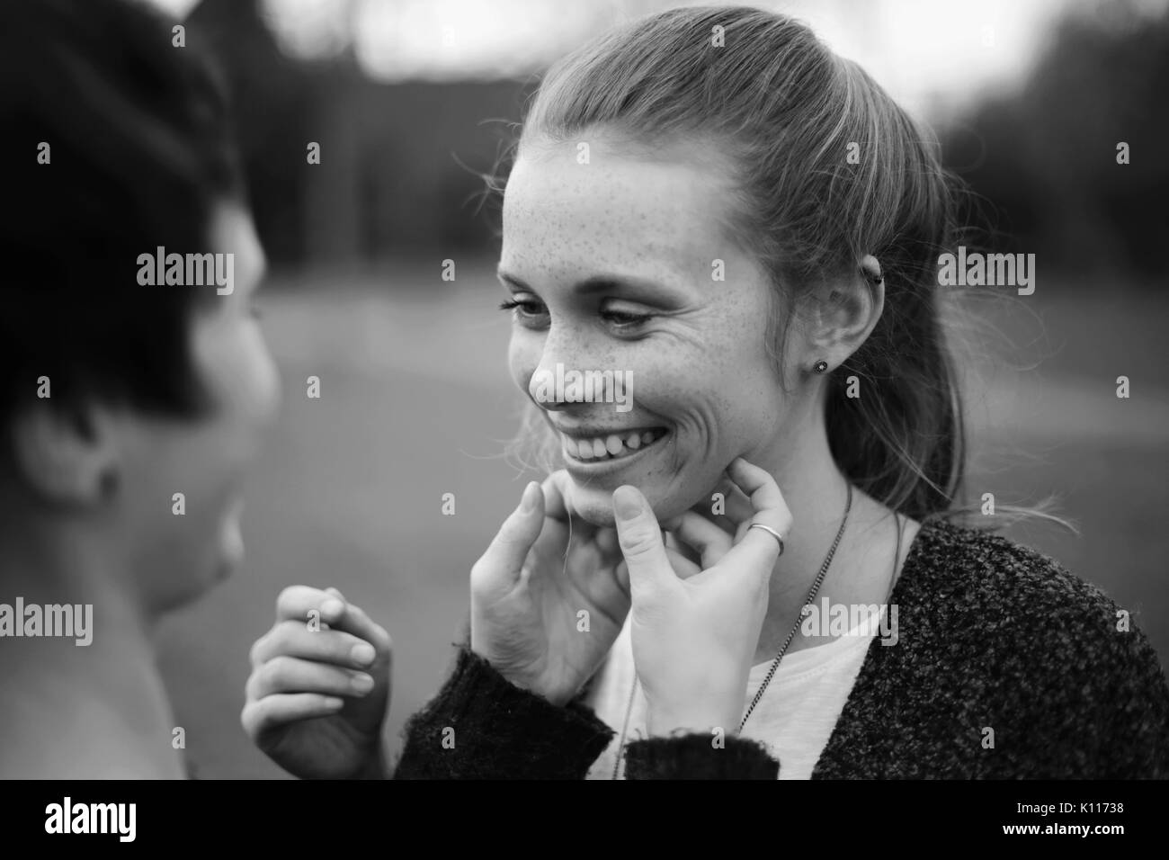 Young woman tickles the face of her friend - Stock Image