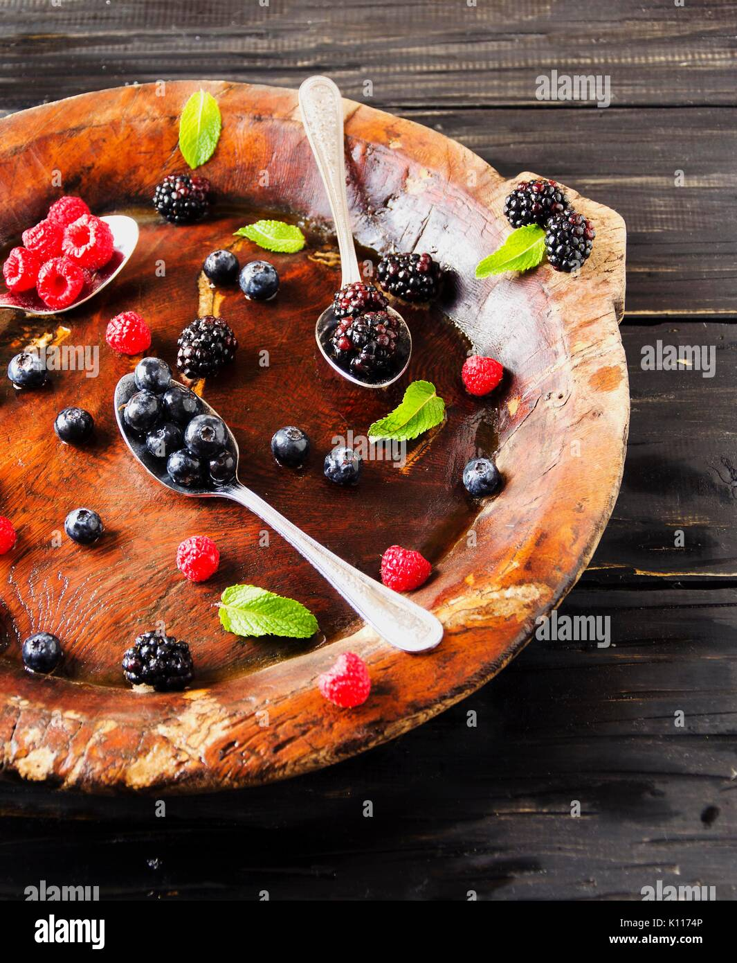 fresh ripe berries raspberries blackberries and blueberries on a brown wooden plate with a spoon on a black wooden table, rustic, selective focus, spa - Stock Image