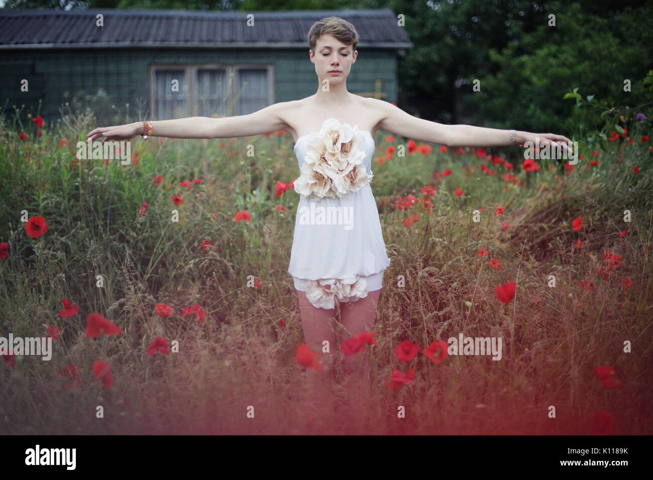 Young woman dancing in a garden - Stock Image