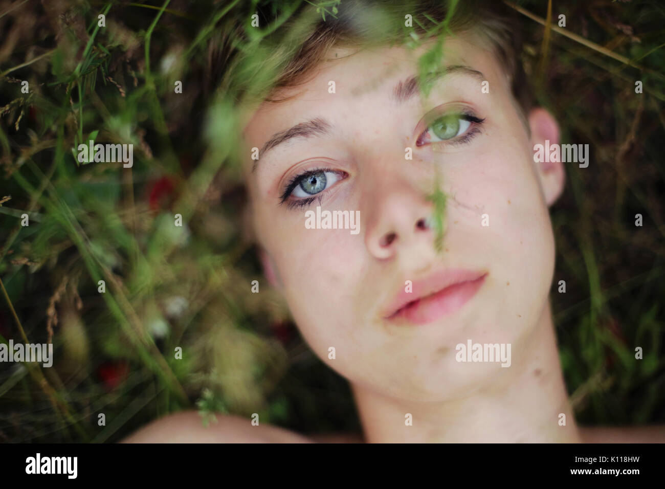 Sad woman lies in the grass - Stock Image