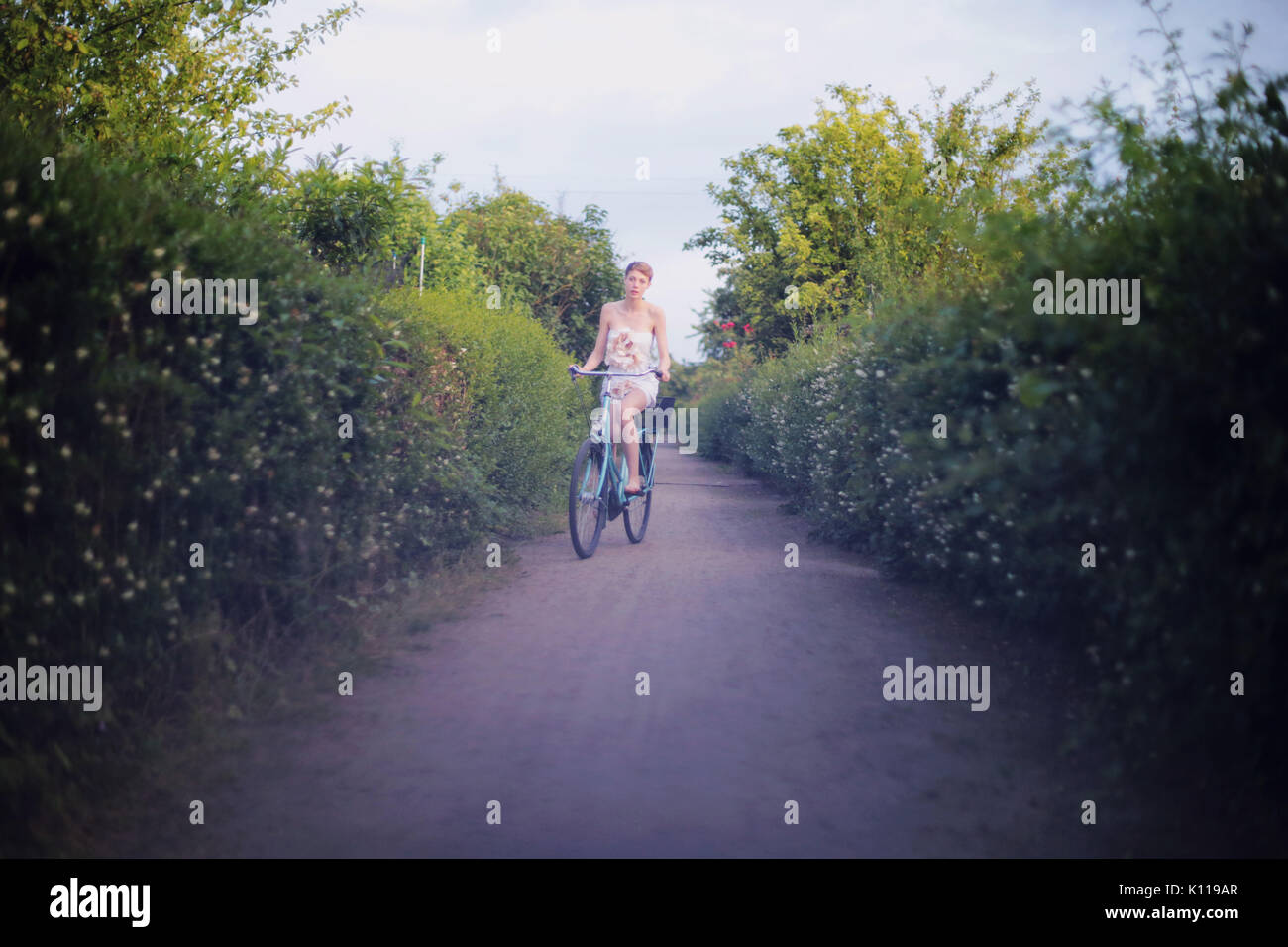 Young woman riding a bicycle in allotments - Stock Image
