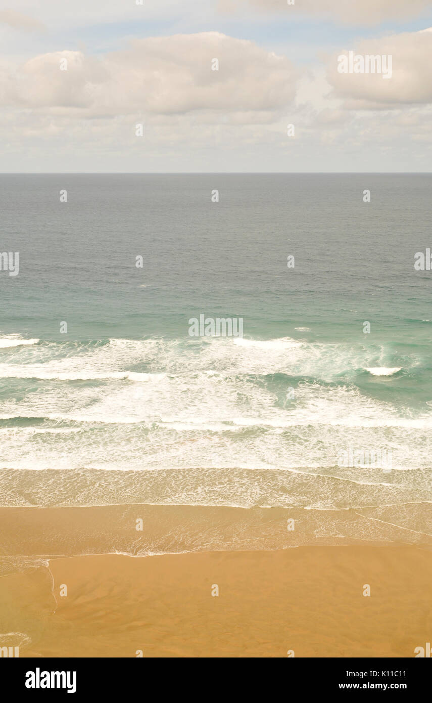the sea and sand washing up on the beach in surf and breakers and sandy beach clear waters on the Cornish coast with clouds in the sky and waves - Stock Image