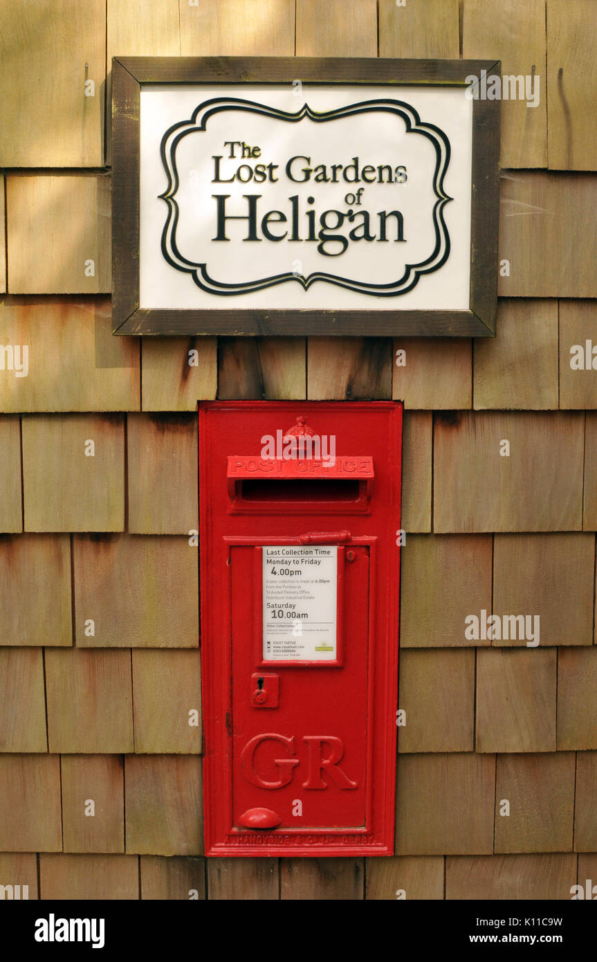 An old red posting box at the lost gardens of heligan in Cornwall Victorian or Edwardian postal services for visitors and tourists convenience handy - Stock Image