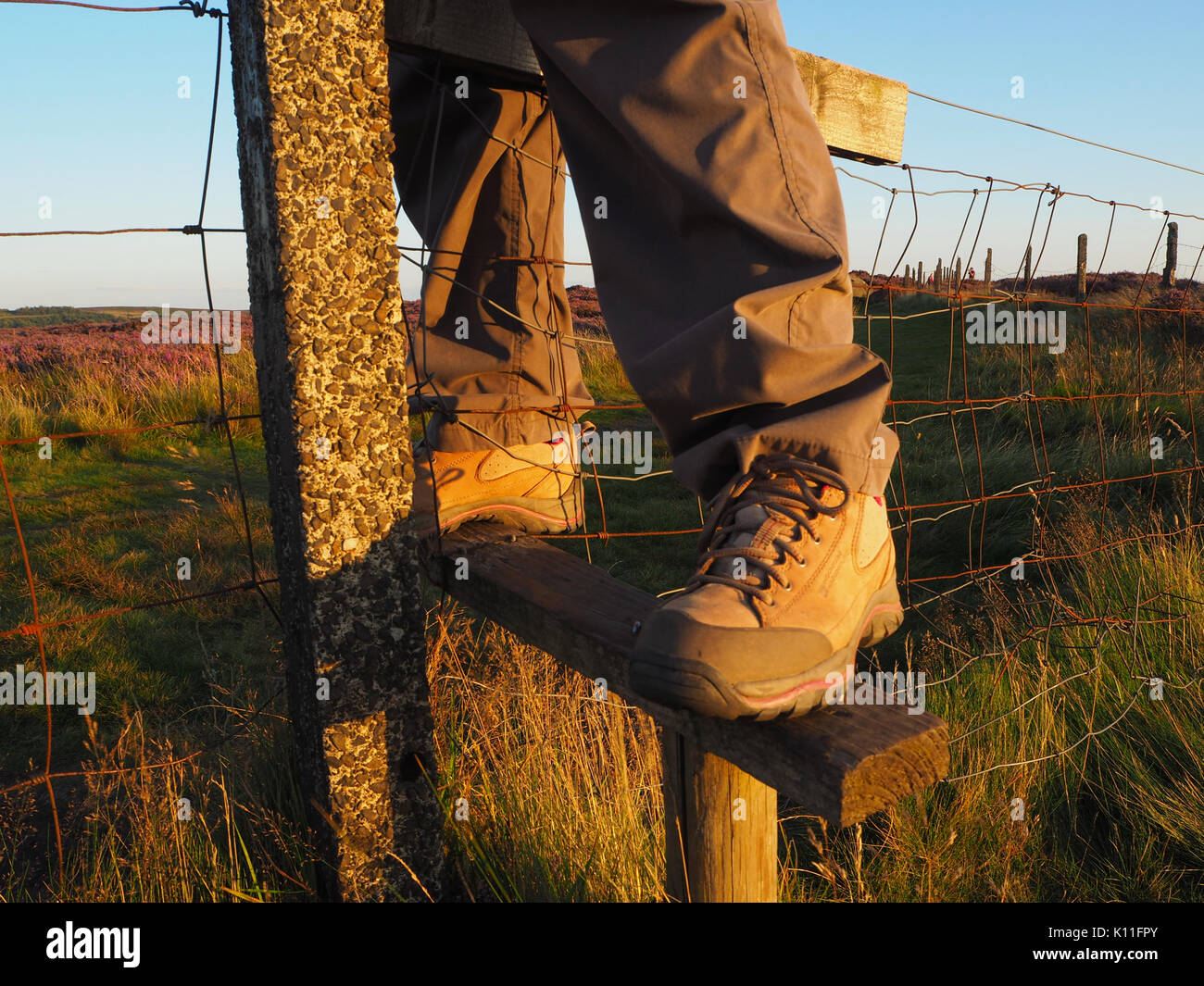 A walker crossing a wire fence in the High Peak - Stock Image