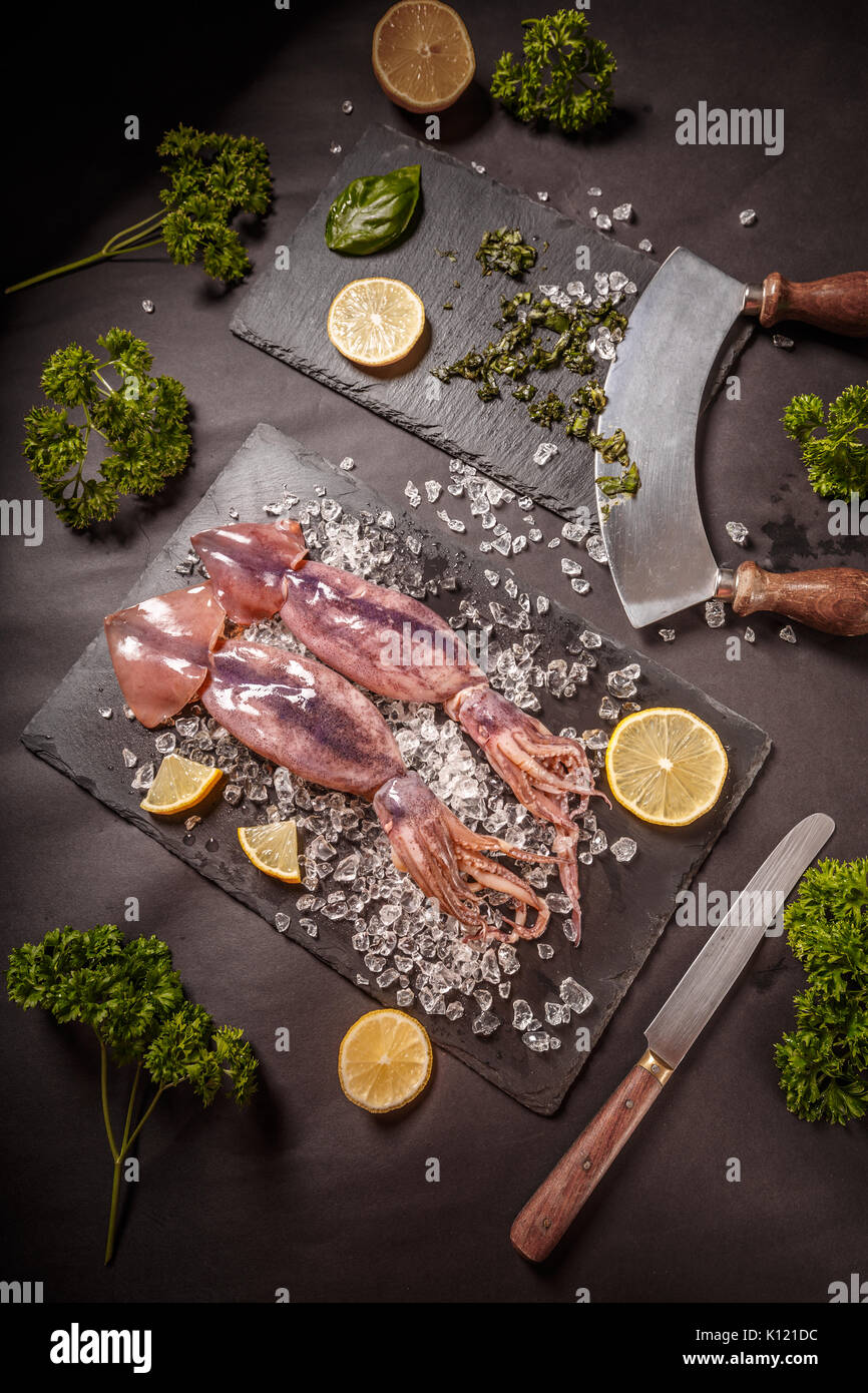 Fresh raw squid with crushed ice and lemon - Stock Image