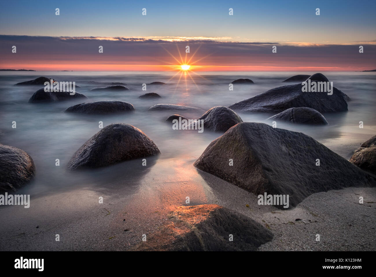 Scenic view from beach with stones and sunset at summer night in Lofoten, Norway - Stock Image