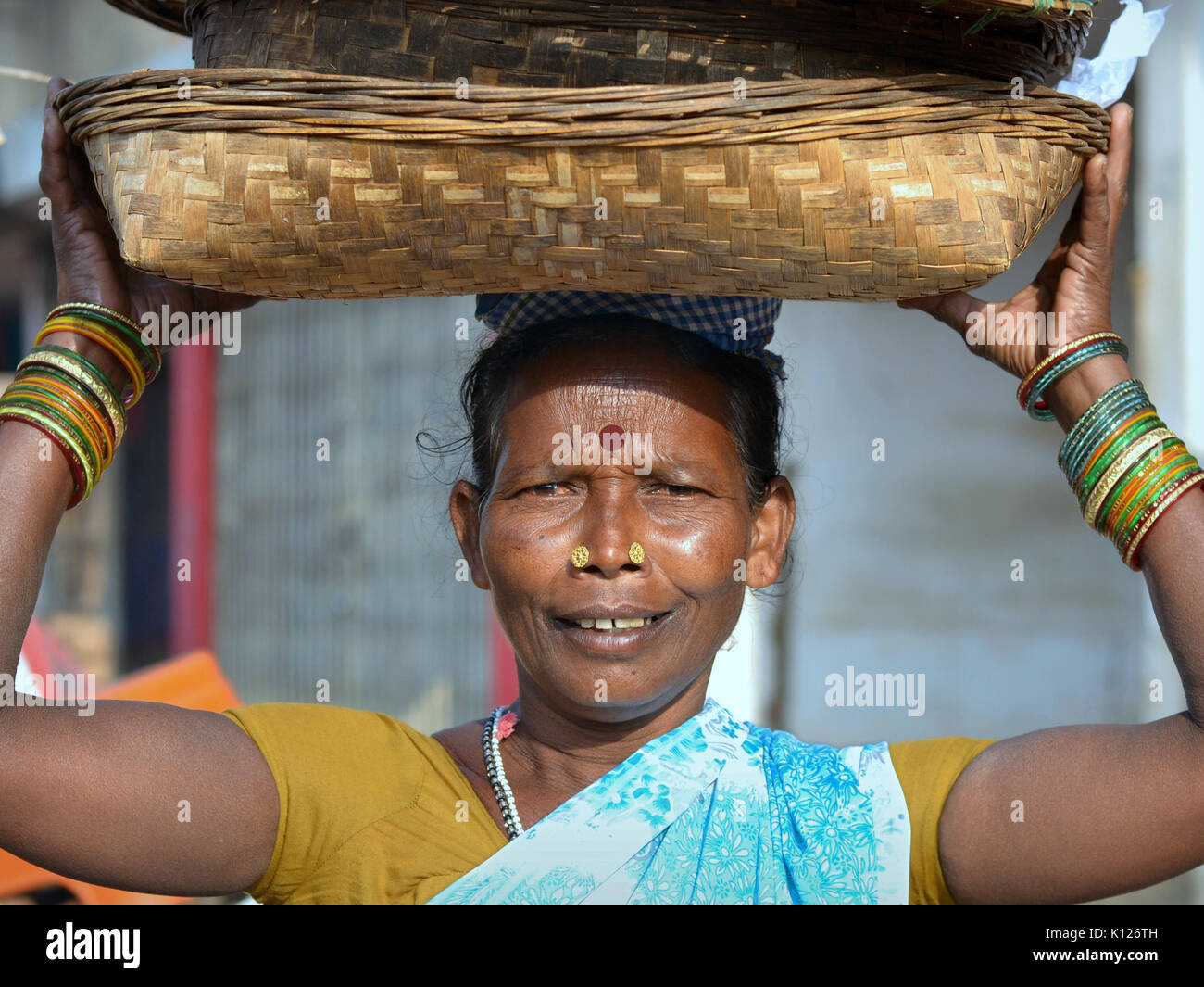 Elderly Indian Adivasi woman (tribal woman) with two distinctive golden nose studs, carrying on her head a set of - Stock Image