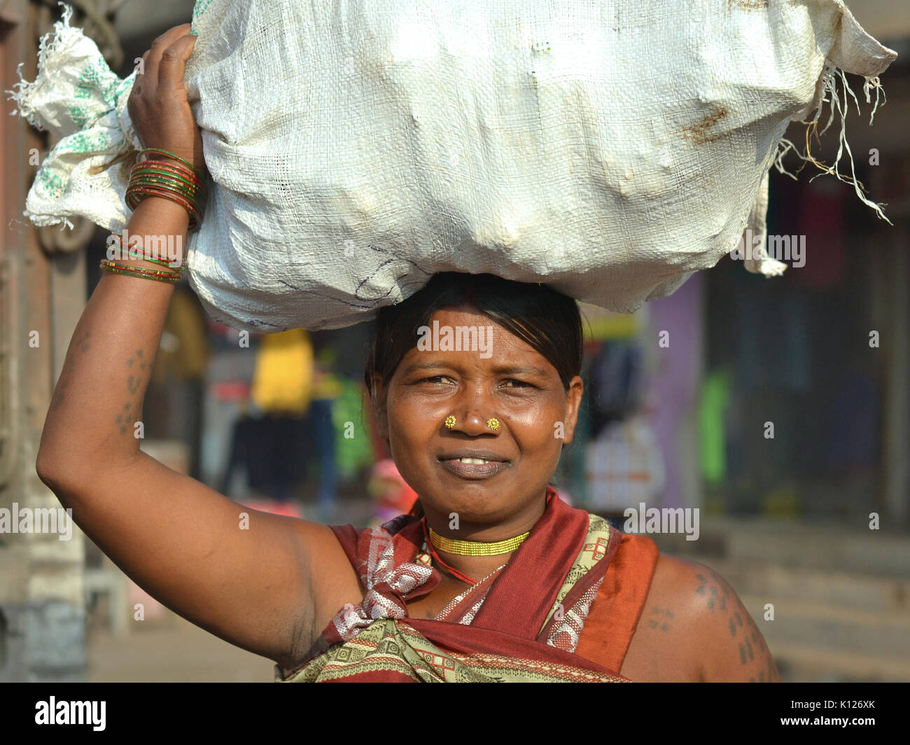 Mature Indian Adivasi woman (tribal woman) with two distinctive golden nose studs, balancing  on her head a heavy - Stock Image