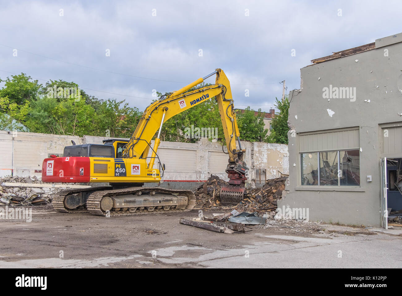 Heavy equipment demolishes and old building in downtown Orillia Ontario to make way for new condominiums. - Stock Image