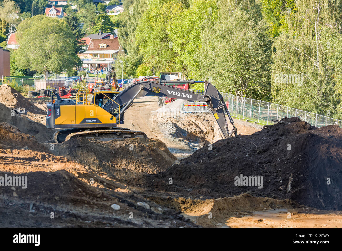 Heavy duty Volvo EC250EL excavator digging and moving piles of topsoil at building site ahead of construction  Model Release: No.  Property Release: No. - Stock Image