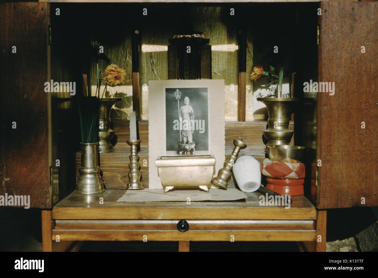 Altar with incense, a printed image, brass candle holders, candles and flowers, inside a wooden cabinet, Japan, 1952. - Stock Image