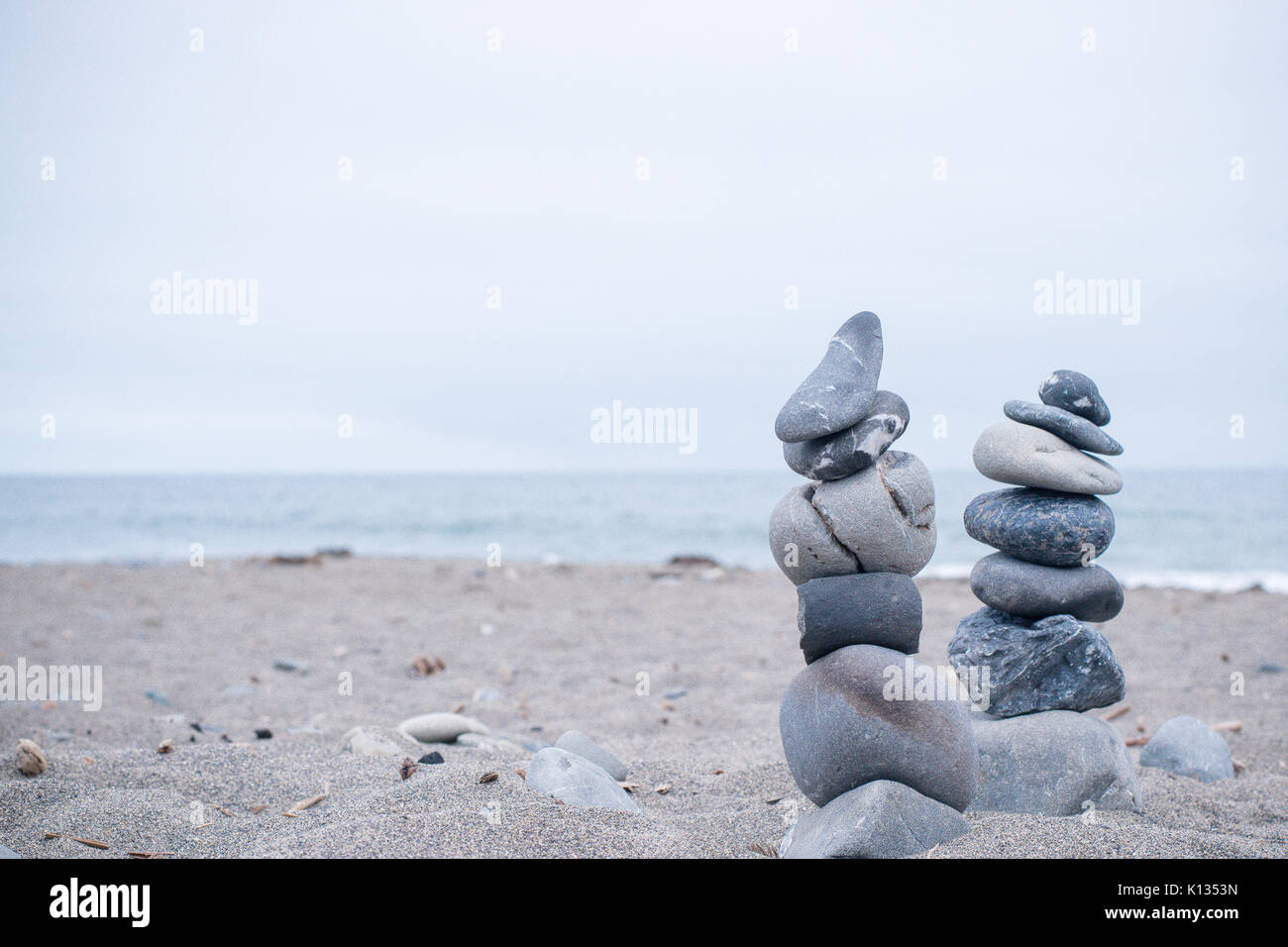 Monochrome, Serene, Blue Stacked rocks on a California beach symbolizing Peace, Balance, Meditation, and Mindfulness - Stock Image