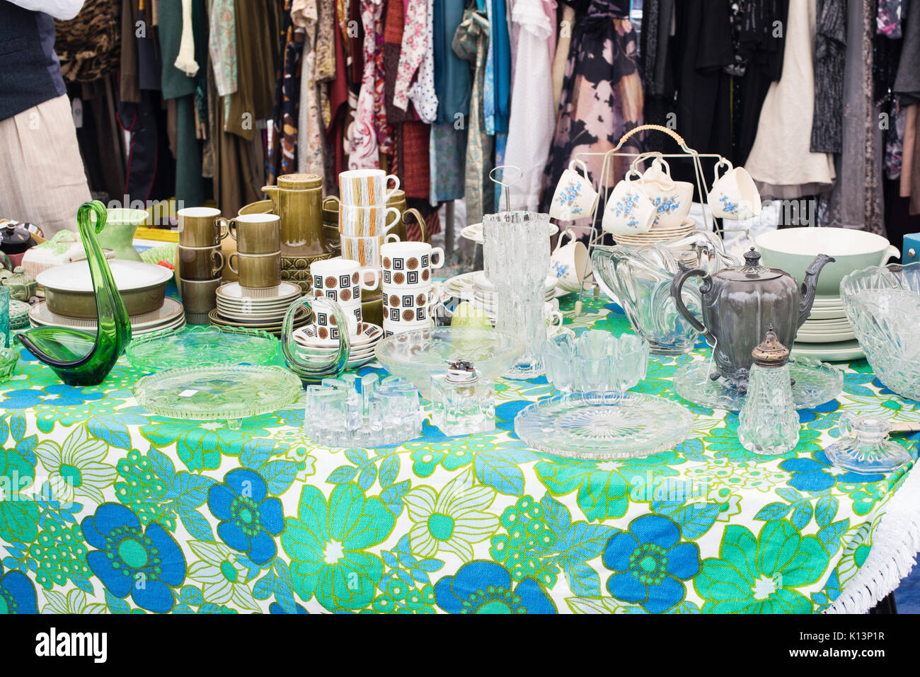 Old fashioned english tableware items and clothes on a rail at a vintage retro festival. UK - Stock Image