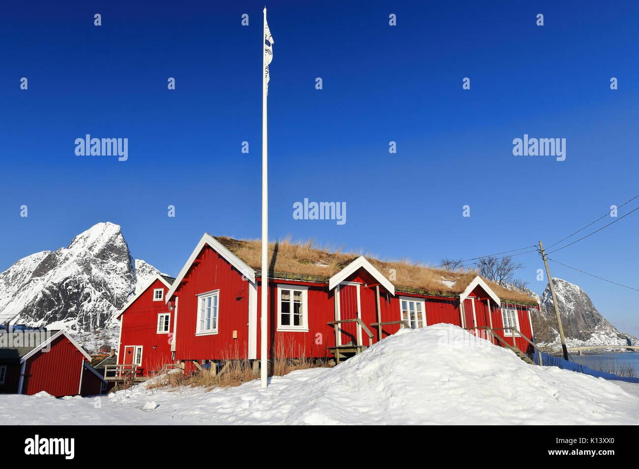 Red wooden cottages or rorbuer-once traditional seasonal fishing huts-now for tourist use-Reine village. Rostadtinden-Olstinden-Festhaeltinden mounts  - Stock Image