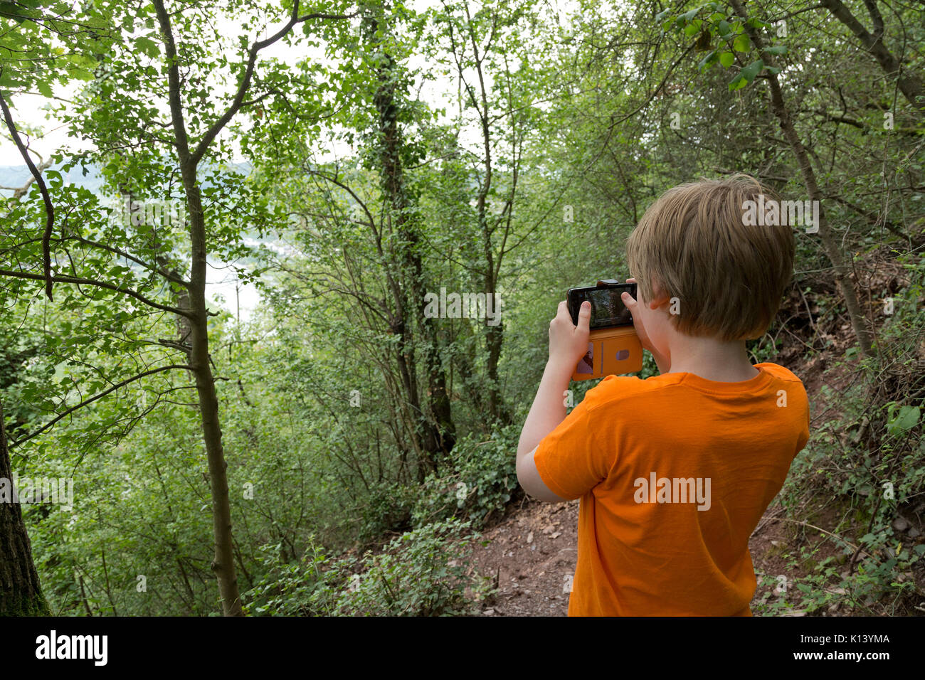 young boy taking photos on fixed rope route, Uerzig, Moselle, Rhineland-Palatinate, Germany - Stock Image