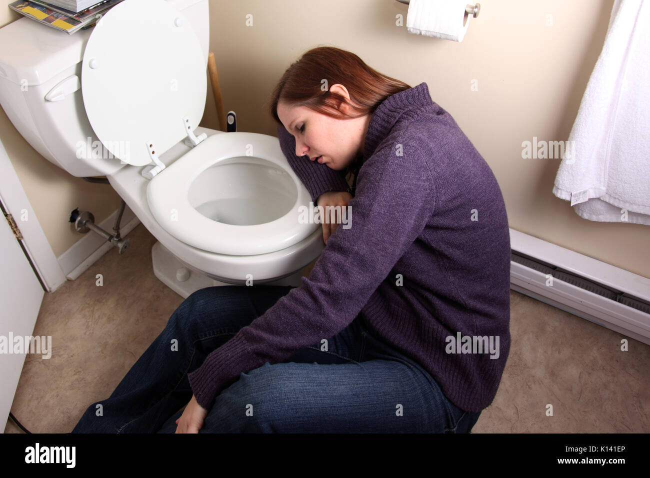 Young Woman Slumped Over Toilet Bowl
