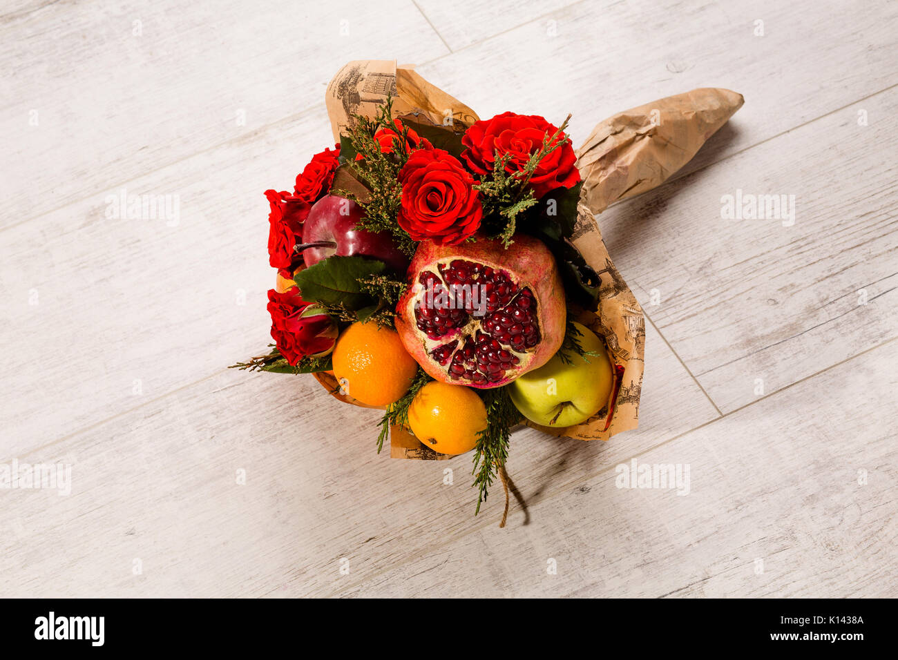 Prettily wrapped composition of red roses and fruits. - Stock Image