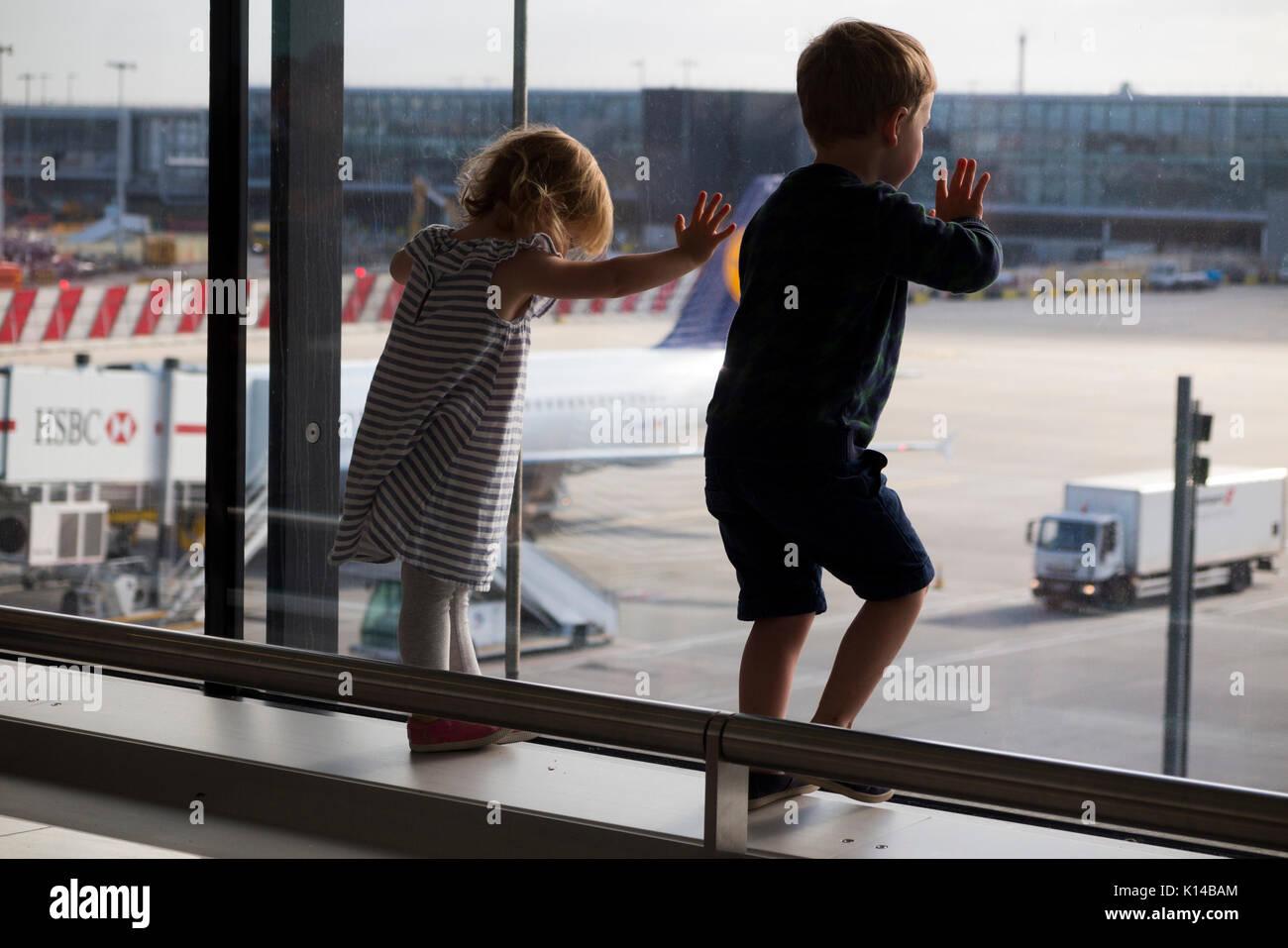 Children wave goodbye to departing aircraft at London Heathrow airport, Terminal 2. UK. (89) - Stock Image