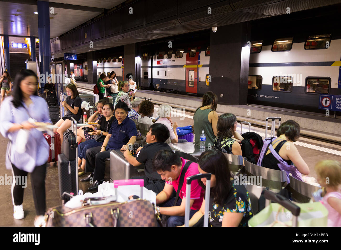Railway platform at Geneva International airport filled with people passengers who have just flown in to Switzerland and you are waiting for a train. - Stock Image